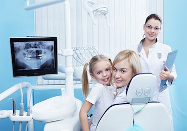 Mother and daughter with doctor smiling at camera