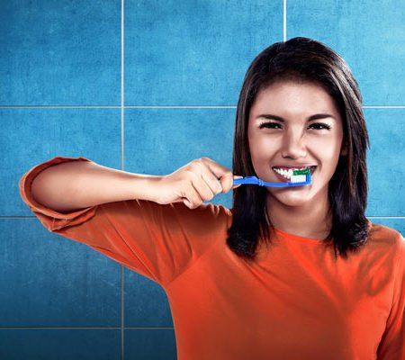 A Lady brushing teeth in front of tiles