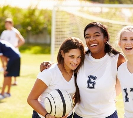 Members of Female High School Soccer Team smiling.